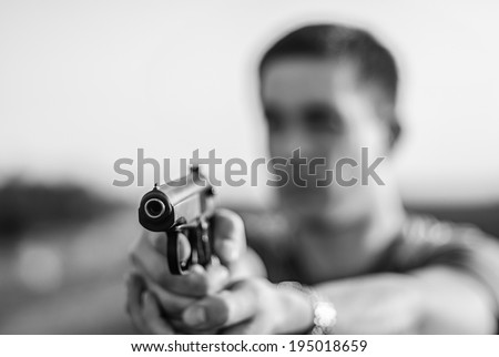 young man took aim with pistol near village roads. - stock photo