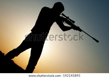 young man took aim with your sniper rifle at sunset. - stock photo