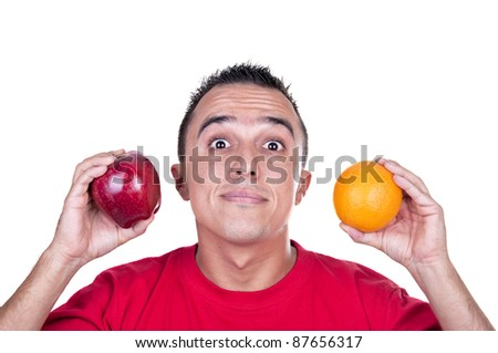 young man torn between an apple and an orange - stock photo