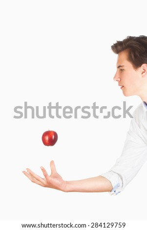 Young Man Tossing Red Apple in the Air  - stock photo