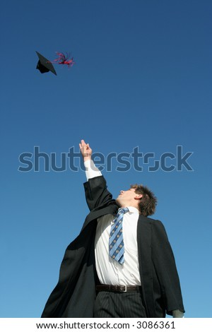 Young man tossing up his hat on Graduation Day - stock photo