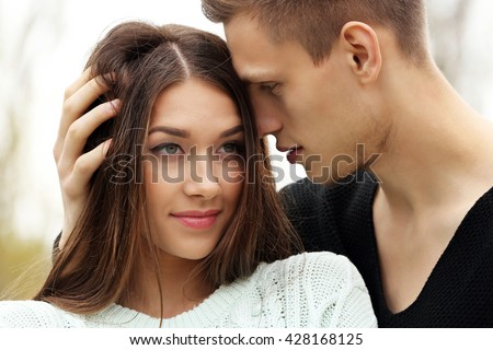Young man touching hair of young woman - stock photo