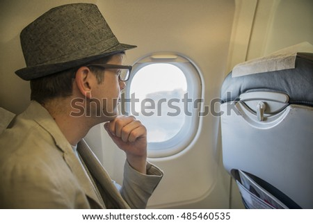 young man tourist sits on the plane near the window and looks