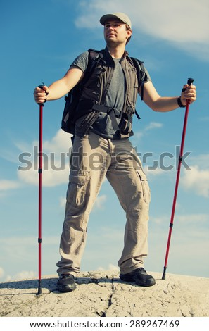 Young man tourist with backpack and sticks standing on mountain top. - stock photo