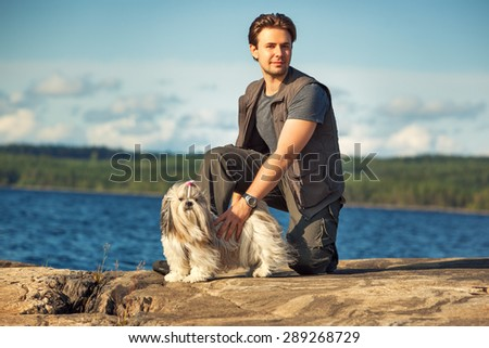 Young man tourist with shih-tzu dog on lake shore. - stock photo