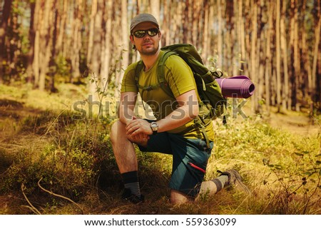 Young man tourist with sunglasses and backpack portrait in forest
