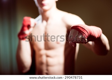 Young man training box punches with bandages closeup on strong muscles of torso over dark studio background