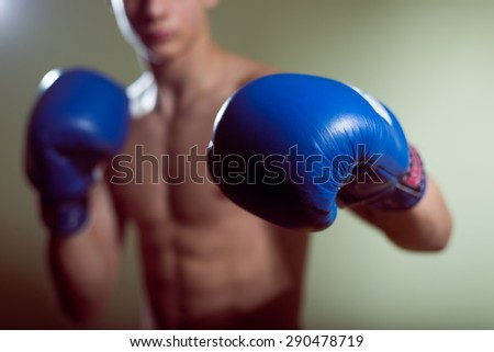 Young man training box punches with blue gloves closeup on strong muscles of torso over dark studio background