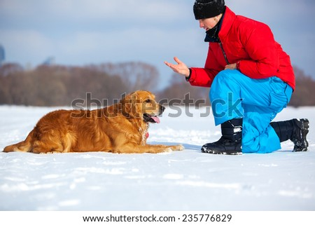 Young man training dog. Cold winter season. - stock photo