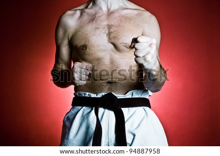 Young man training karate over red background. Fitness and sport concept at gym.