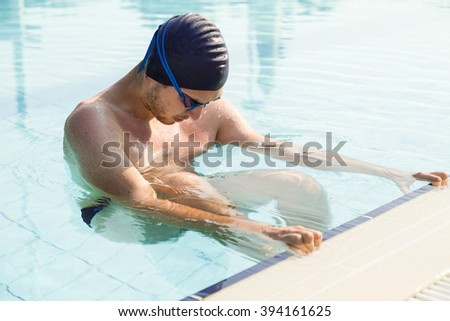Young man training on a swimming pool - stock photo