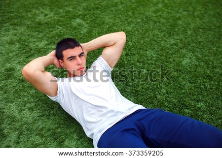 Young man training outdoors and doing sit-ups on green grass.