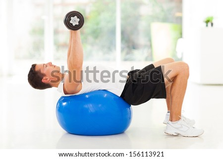 young man training with dumbbells lying on a fitness ball