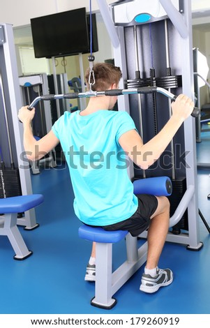 Young man training with weights in gym  - stock photo