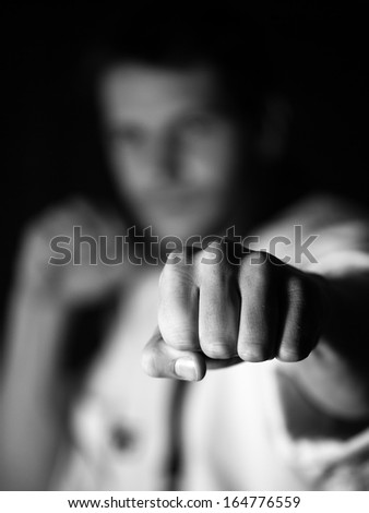 young man trains blow a hand, the washed-away background - stock photo
