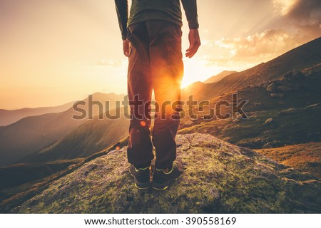 Young Man Traveler feet standing alone with sunset mountains on background Lifestyle Travel concept outdoor  - stock photo