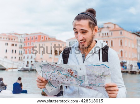 young man traveler with a beard is standing with a map on the street and looking for the way on the map, tourist,outdoor portrait - stock photo