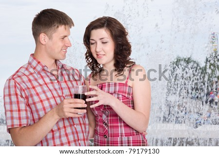 Young man treats his girlfriend to a cool drink. In the background, splash fountain. Hot summer. - stock photo