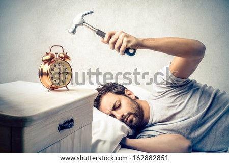 young man tries to break the alarm clock with hammer - stock photo