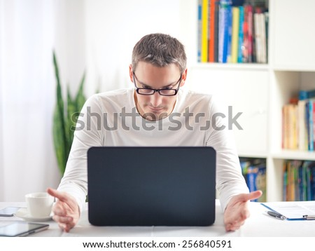 Young man trying to solve problems while working at home using laptop.