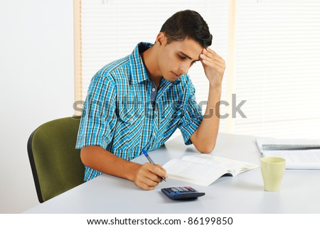 Young man trying to study with a headache.
