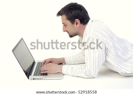 Young man typing and looking at screen of laptop