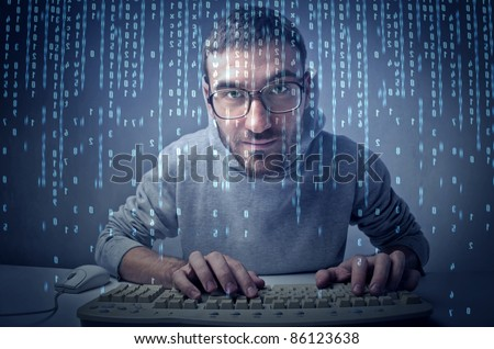 Young man typing on a keyboard in front of a computer screen - stock photo
