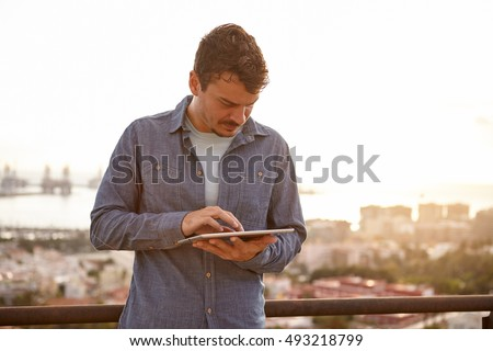 Young man typing on his tablet in deep concentration while standing on a bridge with the sun setting behind him