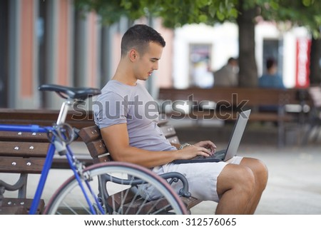 Young man typing on laptop keyboard while sitting on the park bench with his bicycle beside him  - stock photo