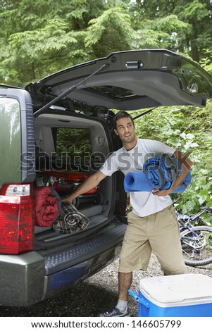 Young man unloading cropped car in the forest - stock photo