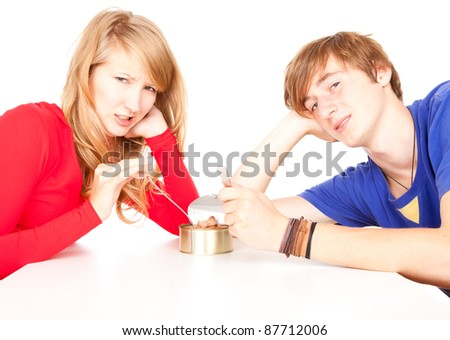 young man unlocks tinned food, white background - stock photo