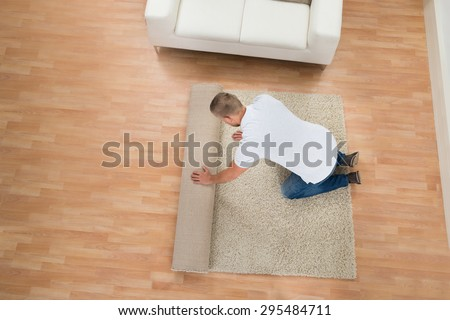 Young Man Unrolling Carpet In Living Room - stock photo