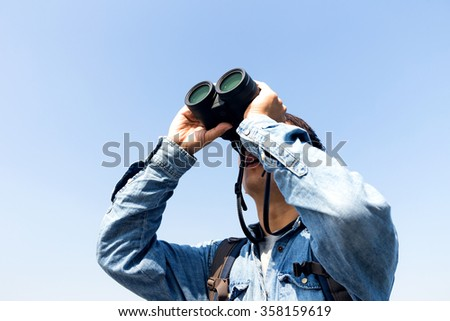 Young Man use of the binocular and looking up