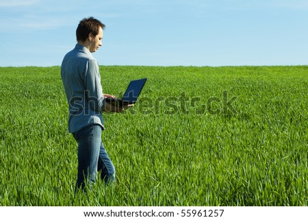 young man uses a laptop in the green field - stock photo