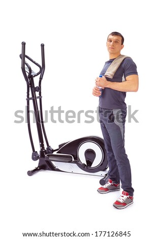 Young man uses elliptical cross trainer. - stock photo