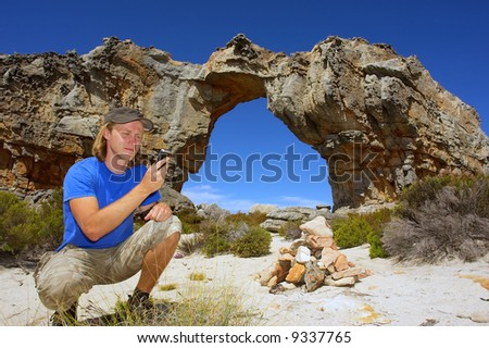 Young man uses phone/gps/handheld pc in mountains. Shot in Wolfberg Mountains, Cederberg, Western Cape, South Africa.