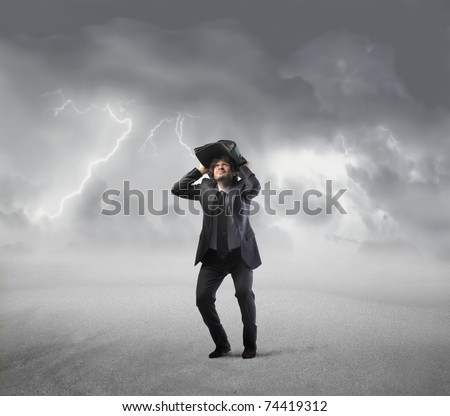 Young man using a briefcase as shelter with stormy sky in the background - stock photo