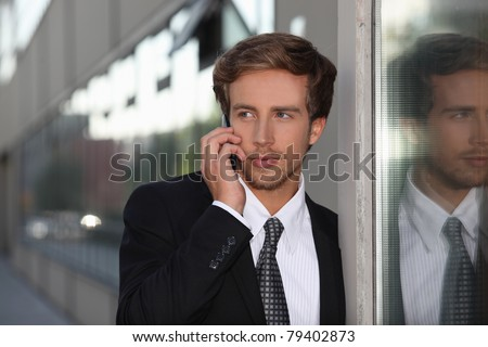 Young man using a cellphone in the city - stock photo