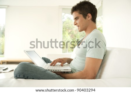 Young man using a laptop computer while sitting down on a sofa at home. - stock photo