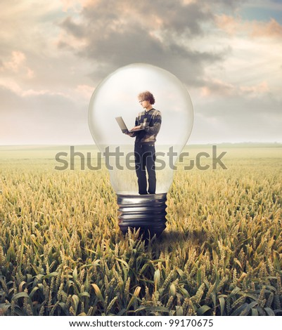 Young man using a laptop in a light bulb on a wheat field - stock photo