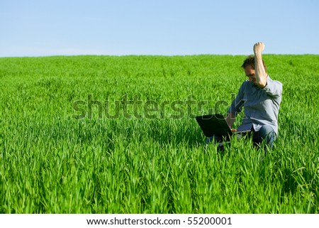 Young man using a laptop outdoors - stock photo