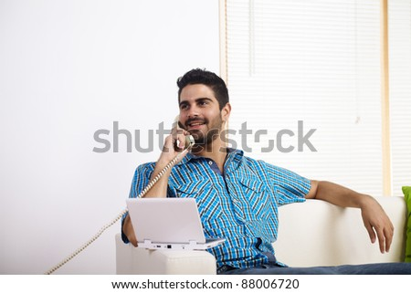 Young man using a laptop while on the phone. - stock photo