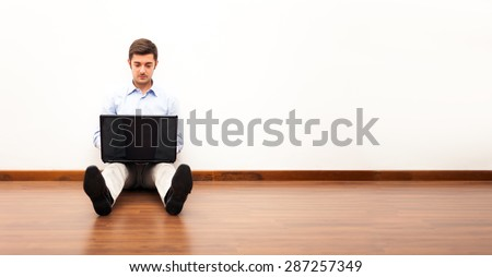Young man using a laptop while sitting on the floor - stock photo