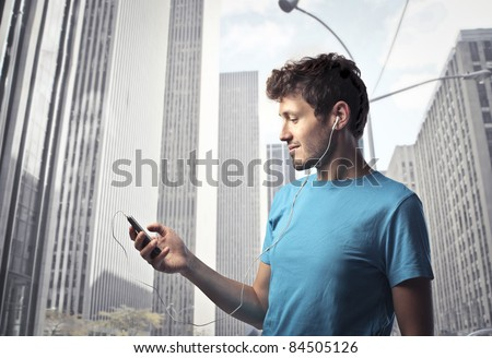 Young man using a mobile phone with cityscape in the background - stock photo