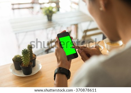 Young man using a smartphone and texting in a cafe - stock photo