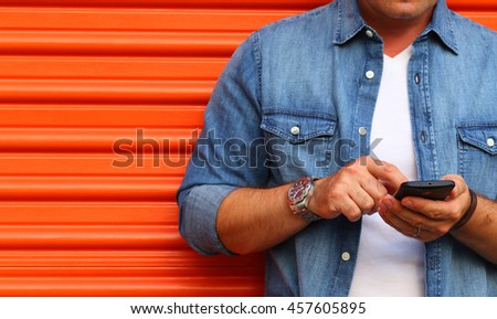 Young man using a smartphone in front of an orange garage door, Dressed casually in jeans. Urban life style, technology, dating, online, business, shopping, fashion and job hunting concept.
