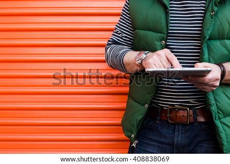 Young man using a tablet in front of an orange garage door, Dressed casually. Jeans, Vest. Urban life style, technology, online, business, shopping, fashion and job hunting concept. - stock photo