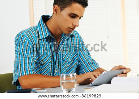 Young man using a tablet PC in an office.