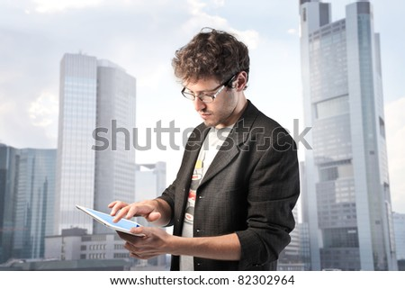 Young man using a tablet pc with cityscape in the background - stock photo