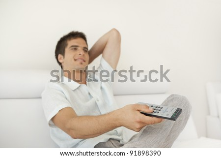 Young man using a tv control remote while sitting on a white leather sofa at home. - stock photo